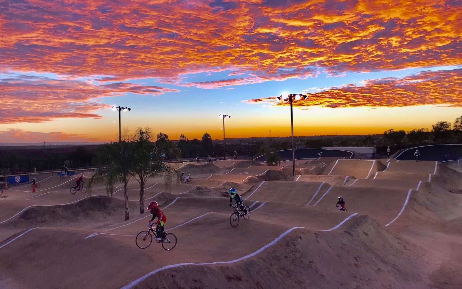 Kids on BMX bikes at sunset