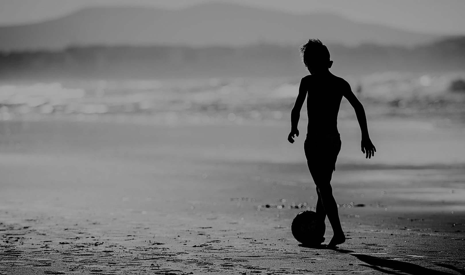Boy with soccer ball on beach.