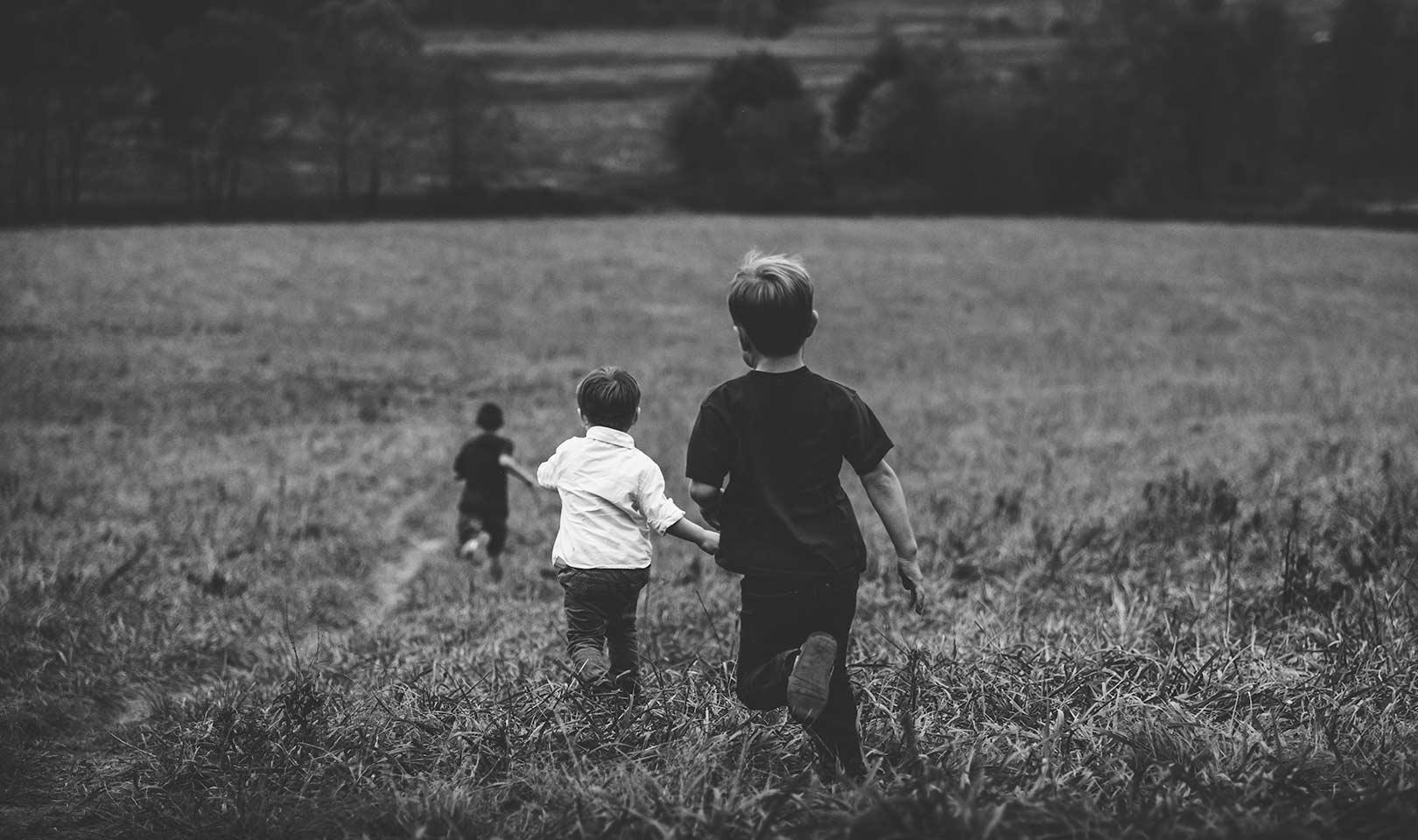 Kids running through a field.