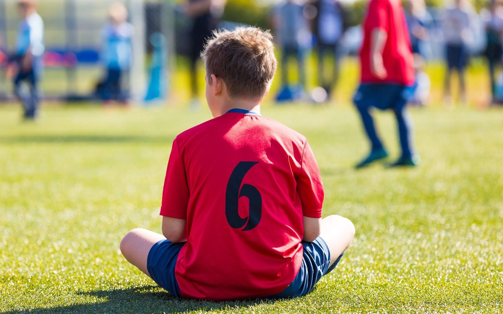 Young soccer player sitting on sports field.